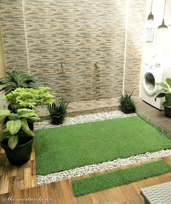 indoor small garden space with grass, pebbles, plants, stone tiles on the wall, wooden tiles on the floor, waching machine