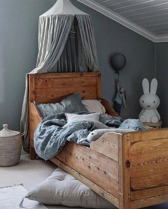 kids bedroom, brown floor, wooden bed, light grey wall, white wooden ceiling, grey canopy, rattan basket, stool