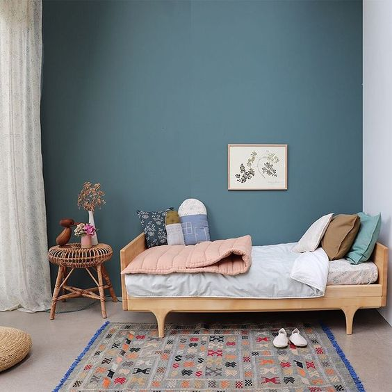 kids bedroom, grey floor, grey rug, green wall, rattan stool, wooden kids bed platform