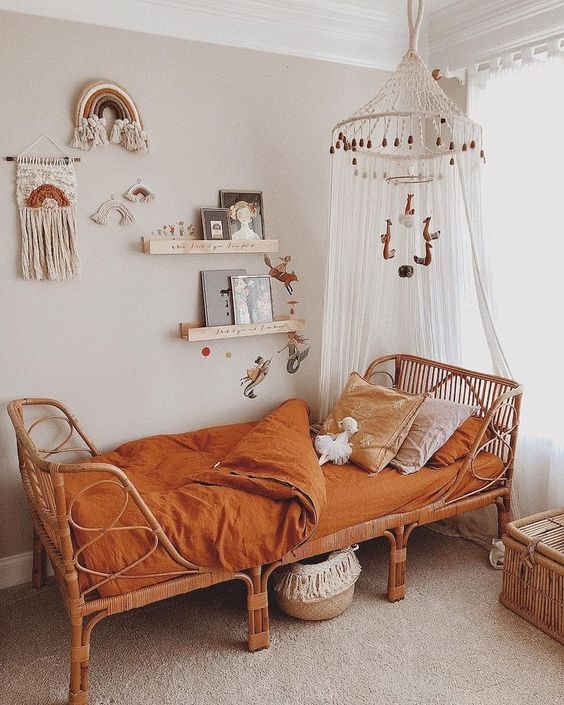 kids bedroom, rug flooring, beige wall, floating shelves, wall decortaion, white bohemian canopy, rattan bed, orange linene