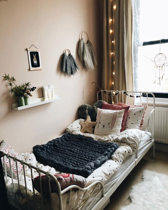 kids bedroom, rug flooring, veige wall, white iron bed, layers of blankets, pillows, floating shelves, brown curtain, fairy lights