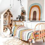 Kids Bedroom, White Wall, Sloping Ceiling, White Wooden Floor, Rattan Bed, Colorful Woven Blanket, Wooden Bookshelves, White Square Cabinets, Plants, Rug
