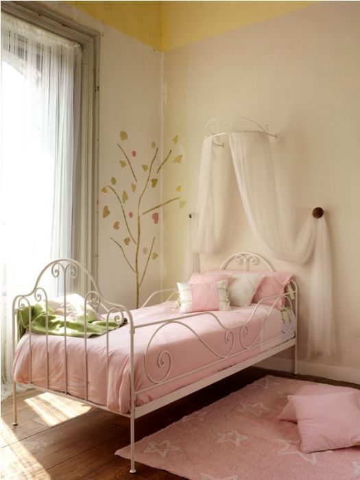 kids bedroom, wooden floor, white iron bed, white canopy, white wall, white curtain, pink bedding, pink rug
