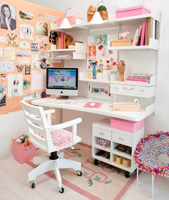 kids study space in white floating table, white floating shelves, white drawers and shelves, pink rug, white wooden office chair, orange board