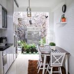 Kitchen And Dining Room With White Gloos Floor, White Wall, Glossy Cabine, Small Garden With Stone Wall