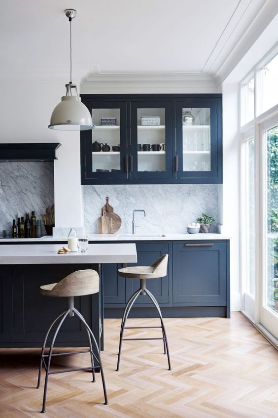 kitchen, chevron wooden floor, dark blue cabinet, white top, white wall, white marble backsplash, white framed glass wall, wooden stool, white pendant