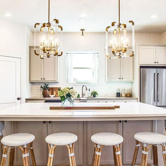 kitchen, island with white porceilain top, white wall, white cabinet, geometric pendants, rattan stool with white round seating
