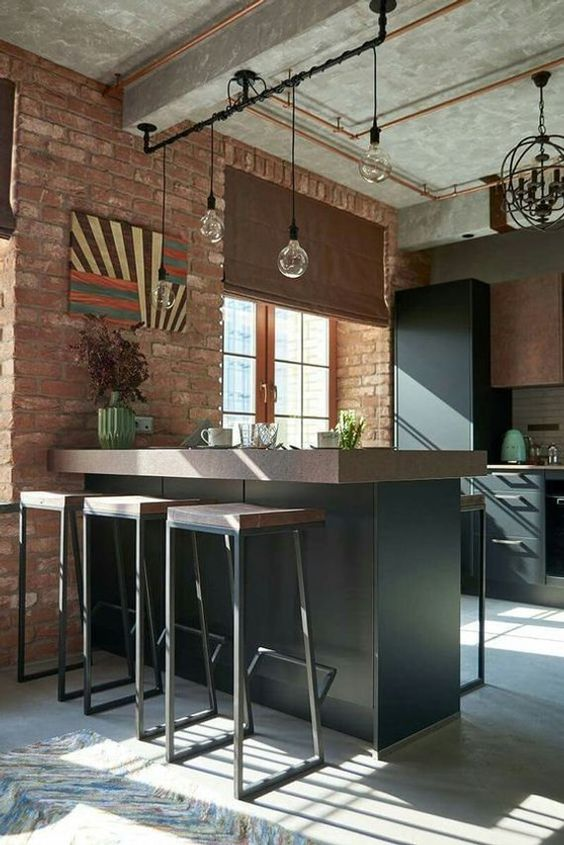 kitchen, open brick wall, chevron floor, black island with brown top, matching stools, black cabinet, brown roman shade, glass pendants, round black chandelier