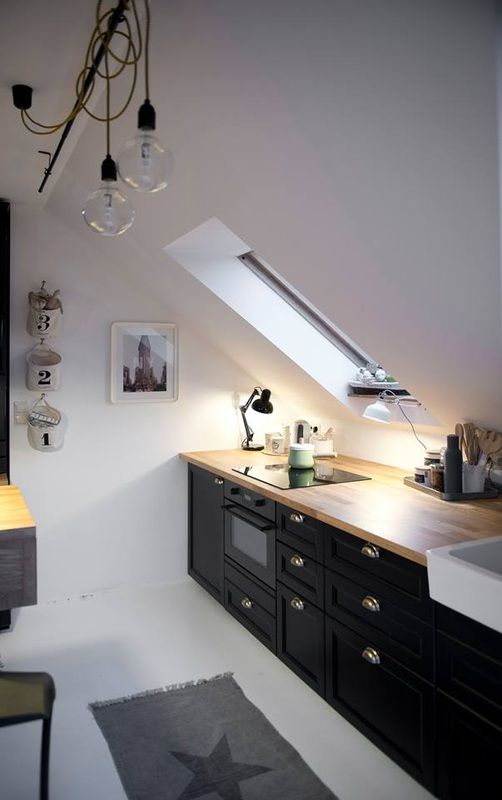 kitchen, white floor, white wall, white sloping wall, black cabinet, wooden top