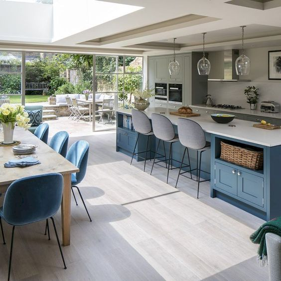 kitchen, white wooden floor, blue wooden island with white top, glass pendant, grey cabinet with white top, blue chairs and brown dining set