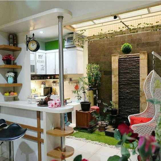 kitchen with white cabinet, white floor tiles, white bar island, black stools, small indoor garden, rattan swing