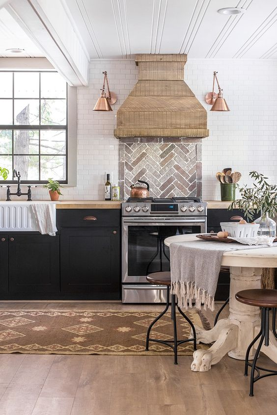kitchen, wooden floor, brown rug, white round dining table, brown sool, white subway wall tiles, herringbone tiles backsplash, brown hood, copper sconces, black cabinet