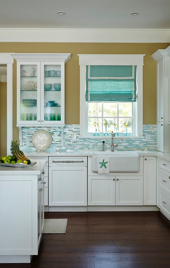 kitchen, wooden floor, white cabinet, warm brown yelow wall, white framed window, blue white backsplash tiles, bue roman shades, white island, white top, white sink