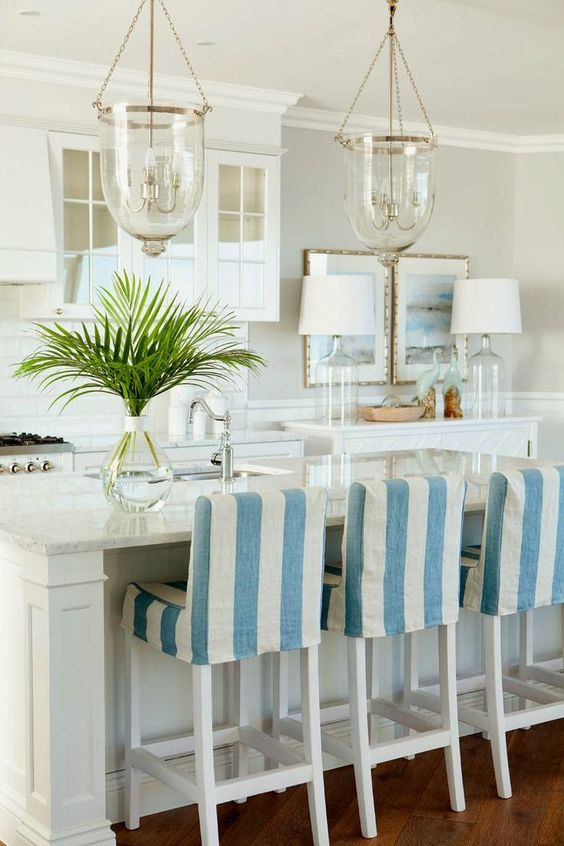 kitchen, wooden floor, white island, white stools with striped blue white cushion, white wall, white ceiling, white kitchen counter top, glass pendants