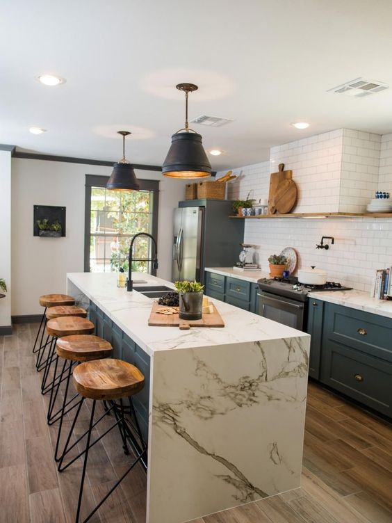 kitchen, wooden floor, white marble island, white subway tiles backsplash, black cover pendants, greenish grey cabinet, wooden round bar stool with black geomterical metal legs