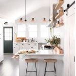 Kitchen, Wooden Floor, White Wall, Sloping Ceiling, Window, Glass Pendants, Sconces, White Cabinet, White Countertop, Floating Shelves