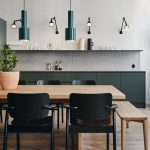 Kitchen, Wooden Floor, Wooden Dining Table Set With Wooden Benches, Black Chairs, White Wall, Grey Backsplash, Floating Shelves, Green Cabinet, Sconces, Hanging Pendant