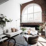 Large Glass Window With Round Top With Extended Legs Shape, White Wall, Stairs, White Sofa, Grey Rug, Chairs,