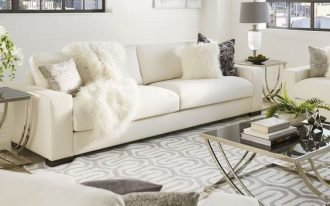 living room, beige floor, white rug, white sofa, white chair, coffee table dark glass top, side tables, table lamp, white wall