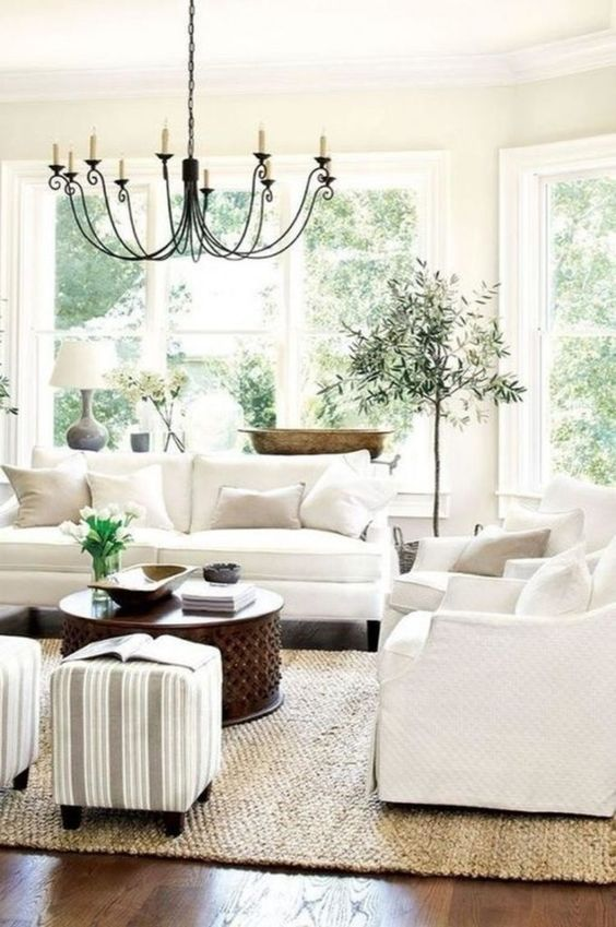 living room, dark wooden floor, white sofa, white wall, white ceiling, black metal chandelier, white ottoman, wooden coffee table