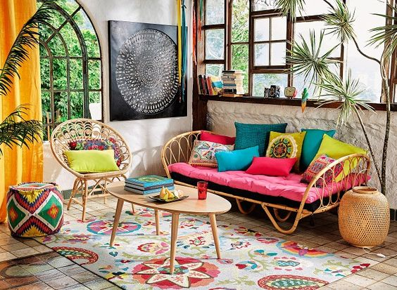 living room, floor tiles, colorful patterned rug, rattan sofa pink cushions, colorful pillows, rattan chairs, colorful ottoman, white wall, windows, plants, wooden coffee table