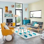Living Room, Grey Floor, Geometric Rug, Grey Sofa, Yellow Chair, Light Blue Wall, Light Green Wall, Floating Shelves. Blue Cabinet, Entertainment Shelves, Nesting Tables
