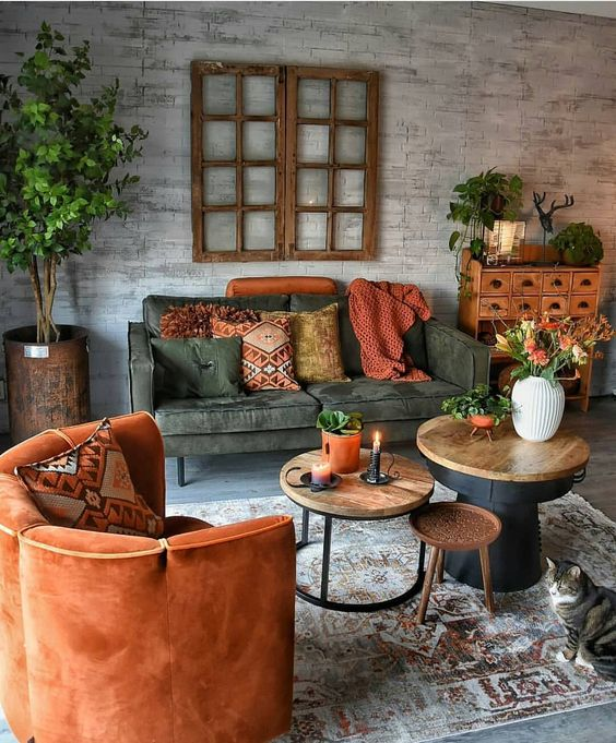 living room, grey floor, rug, grey sofa, grey textured wall, orange chair, orange pillows, wooden cabinet, plants on pot