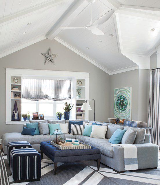 living room, grey rug, grey sofa, stripes ottoman, blue grey square ottoman coffee table, white framed window, shelves, stripes shade, white vaulted ceiling