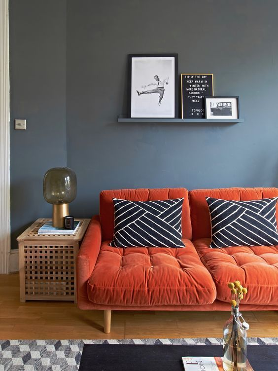 living room, grey wall, wooden floor, woodne side table, orange sofa tufted, gey rug, black coffee table, floating shelf