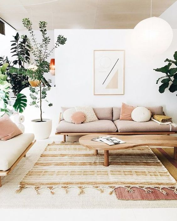 living room, layered rug, white wall, white pendant, wooden sofa with cushion, pillows, plants