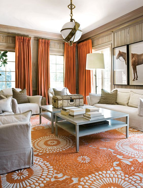 living room, orange rug, white sofa and chairs, brown wall, white ceiling, white pendant, orange curtains