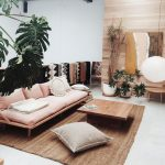 Living Room, White Floor, Natura Rug, White Wall, Wooden Wall, Wooden Sofa With Cushion, Plants, Square Wooden Coffee Table