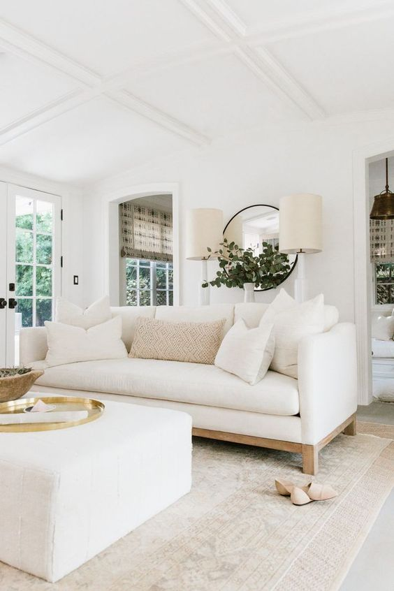 living room, white floor, rug, white sofa, white square ottoman, white wall, white coffered ceiling