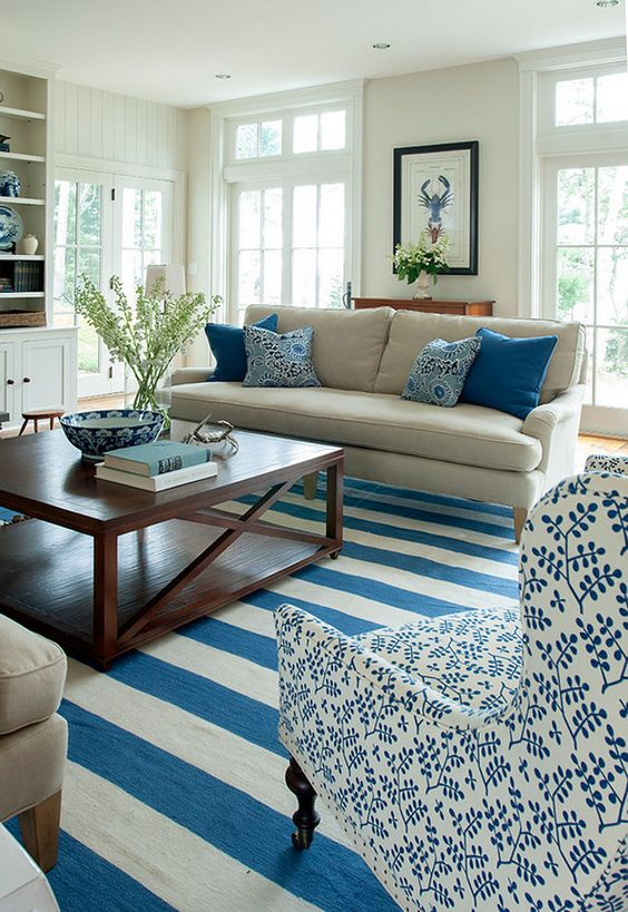 living room with blue white stripes, beige sofa, white blue chairs, wooden square table, white wall, white ceiling, white selves