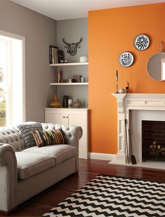 living room, wooden floor, black white rug, grey sofa, grey wall, orange accent wall, white fireplace, white cabinet