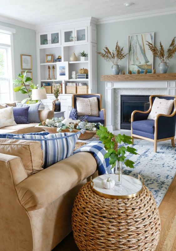living room, wooden floor, blue white rug, brown sofa, rattan side table, blue chairs, white chelves, white fireplace, plants