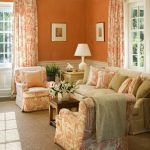 Living Room, Wooden Floor, Brown Rug, Beige Sofa, White Orange Chairs, Orange Painted Wall, White Molding, Windows, Curtain