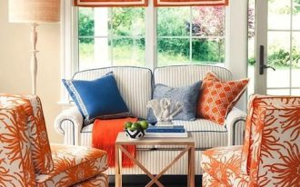 living room, wooden floor, brown rug, white orange chairs, white sofa, off white wall, orange roman shades, glass windows, glass door