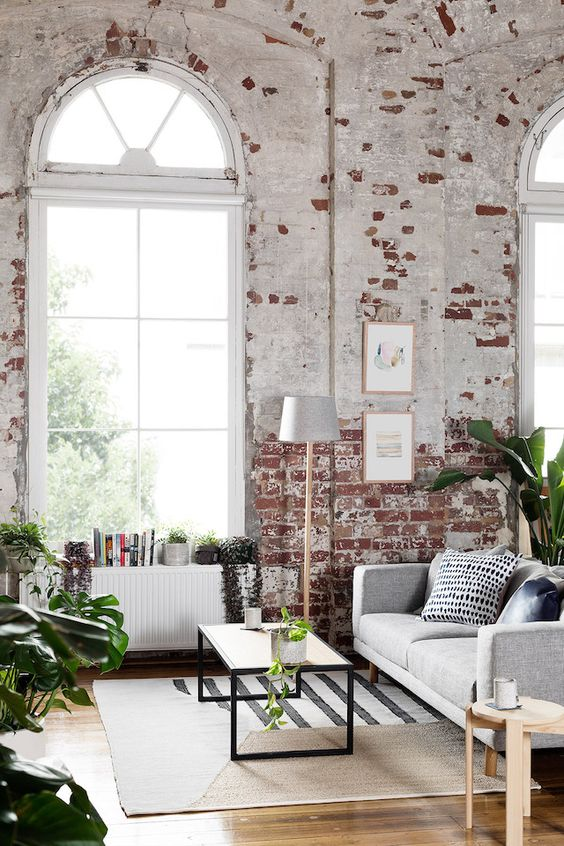 living room, wooden floor, grey sofa, wooden coffee table, open brick wall, large windows, floor lamp