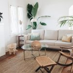 Living Room, Wooden Floor, Natural Rug, Off White Sofa, Rattan Rocking Chair, Rattan Ottoman, Round Coffee Table With Glass Top, White Wall, White Fireplace