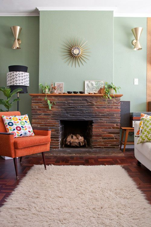 living room, wooden floor, rug, orange chair, white sofa, open brick fire place, green wall, sconces, back floor lamp