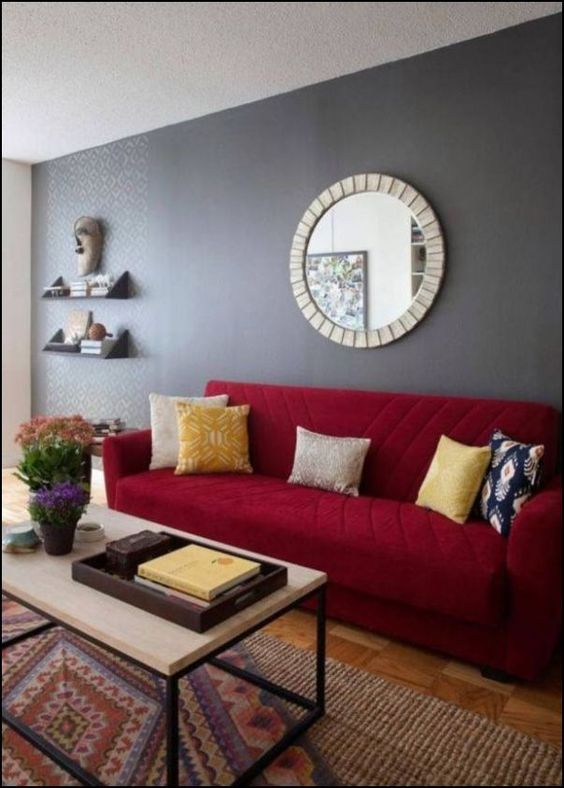 living room, wooden floor, rug, red sofa, white coffee table, grey wall, floating shelves, mirror