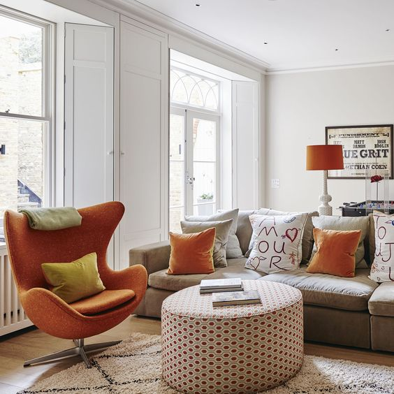 living room, wooden floor, white rug, white round ottoman, light grey sofa, pillows, orange lamp ploor, orange chair, white wall, white ceiling