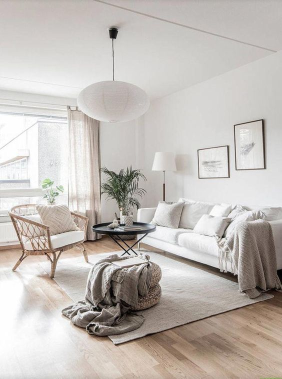 living room, wooden floor, white sofa, rattan chair with white cushion, ottoman , black round coffee table, white wall, white ceiling, white pendant, white floor lamp, white curtain,
