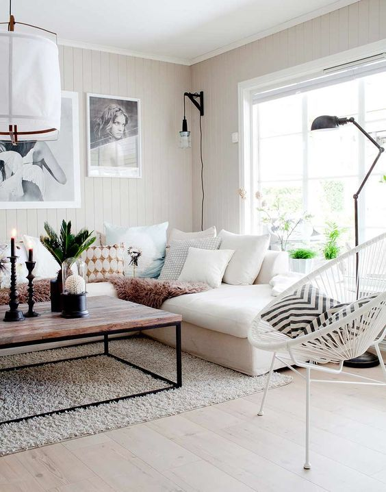 living room, wooden floor, white wooden walls, rug, white corner sofa, wooden coffee table, white rattan, pillows