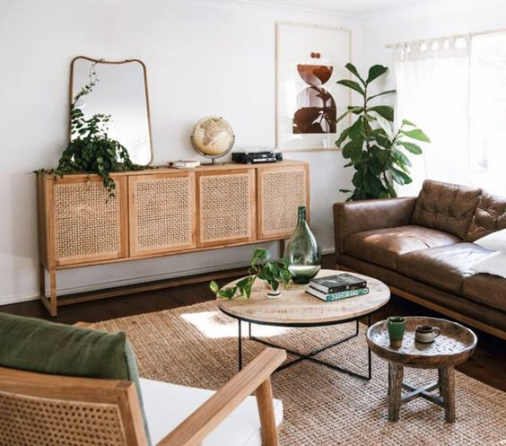 long cabinet with rattan door, wooden floor, rattan rug, brown leather sofa, round wooden coffee tables, wooden chair with cushions, plant, mirror