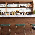 Modern Bar, Wooden Island, White Marble Top, White Wall, Wooden Shelves, Golden Stool With Green Cushion