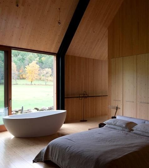 natural bedroom, wooden floor, wooden wall, wooden sloping ceiling, large glass window, white tub