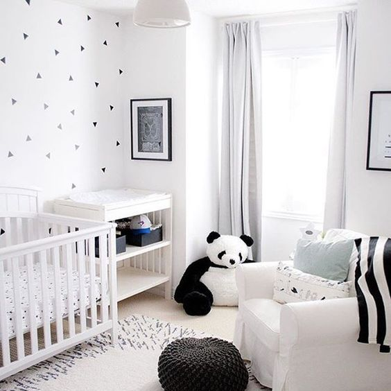 nursery, beige floor, white wall, white curtain, white wooden crib, white chair, stuffed panda, black ottoman, white changing station