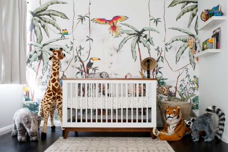 nursery, dark wooden floor, rug, white wooden crib, stuffed animals, forest wallpaper